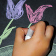A child's hand drawing a flower — Stock Photo