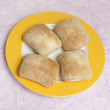 Four ciabatta rolls on yellow and white plate — Stock Photo