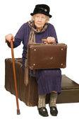 Starsza pani siedzi na walizkę — Zdjęcie stockowe