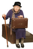 The old lady sits on a suitcase — ストック写真
