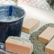 Bucket with concrete and bricks - Stok fotoğraf