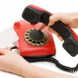 Stock Photo: Girl dials number on red phone
