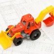 Toy yellow tractor on projects - 