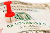 Red thumbtack on a banknote — Stock Photo