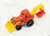 Toy yellow tractor on projects — Stock Photo