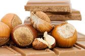 Chocolate and hazelnuts on white — Stock Photo