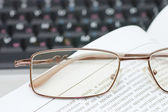 Eyeglasses and books on the laptop — Stock Photo