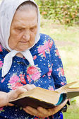 The old woman with the bible — Stock Photo