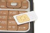 Mobiltelefon och SIM-kort isolerat på vit bakgrund — Stockfoto