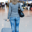 The girl with luggage at the airport - Stock Photo