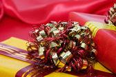 Vakken met geschenken op een rode stof — Stockfoto