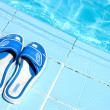 Pretty flip flops by the swimming pool - Stok fotoraf