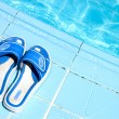 Pretty flip flops by the swimming pool — Stock Photo