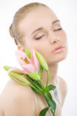 Woman face with a pink flower. — Stock Photo