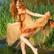 Cheery red-haired woman dancing in the water. — Photo