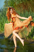 Cheery red-haired woman dancing in the water. — Stock Photo