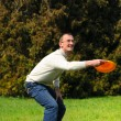Royalty-Free Stock Photo: Handsome young man is playing Frisbee