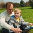 Little boy and his father are reading a book outdoor — Stock Photo