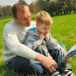 Little boy and his father are reading a book outdoor — Stock Photo #2924662