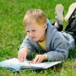 Little boy is reading a book outdoor — Stock Photo