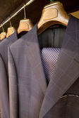 Hanging designer suits — Stockfoto