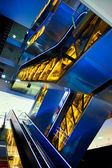 Blue and yellow escalators — Stockfoto