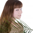 Pretty face of woman hiding behind the big green palm leaf — Stock Photo