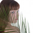 Pretty face of woman hiding behind the bpalm leaf — Stock Photo