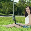 Beautiful woman in a park with laptop — Stock Photo