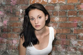 Fashion portrait of young woman with a brick wall — Stock Photo