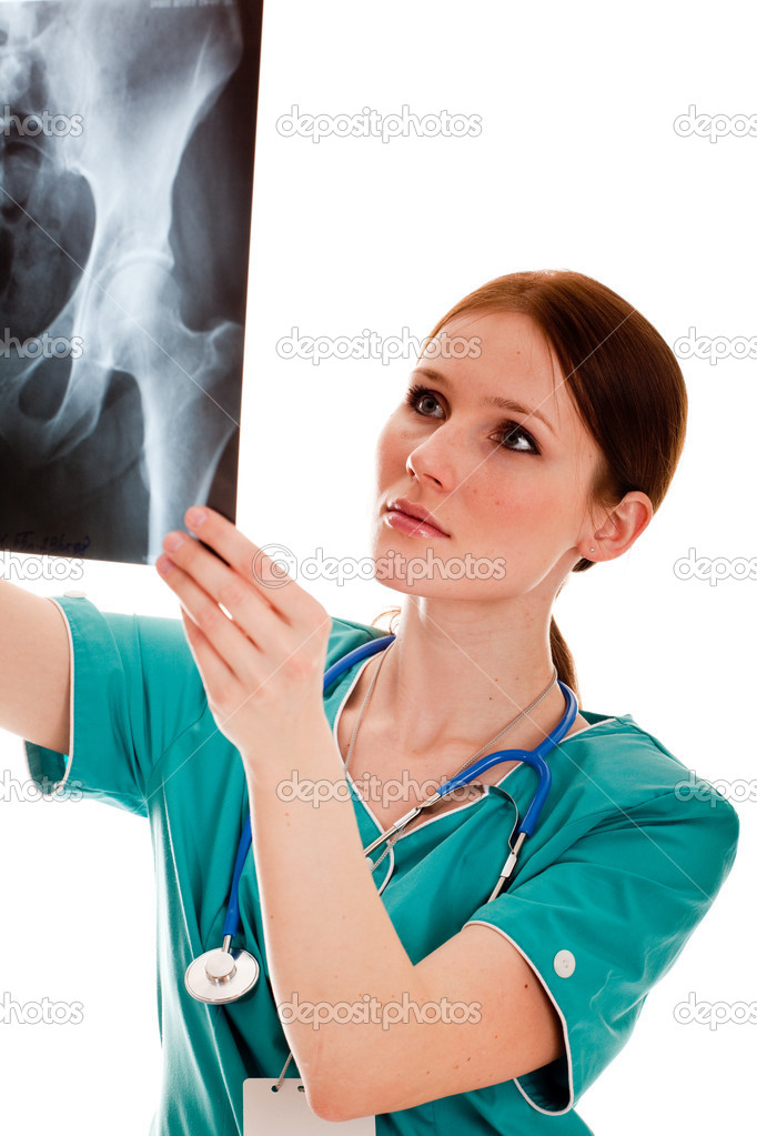 Pretty female doctor in the green uniform looking at the xray picture  Stock Photo #2881019