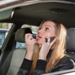 Woman in a car doing makeup - Stock Photo