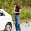 Woman calls to a service standing by a white car — Stock Photo #3239236