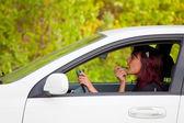 Woman in a car doing makeup. — Stock Photo