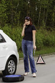 Woman calling to a service standing by a white car — Stock Photo