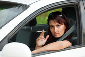 Pretty adult woman sitting in a car and smoking a cigarette — Stock Photo