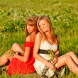 Pretty girls sitting on a beautiful meadow — Stock Photo