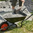 Stock Photo: Somebody filling wheelbarrow with grey sand