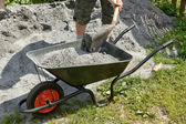 Somebody filling the wheelbarrow with a grey sand — Stock Photo