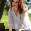 Stock Photo: Pretty young woman with a laptop at park