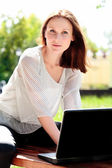 Pretty young woman with a laptop at park — Stock Photo