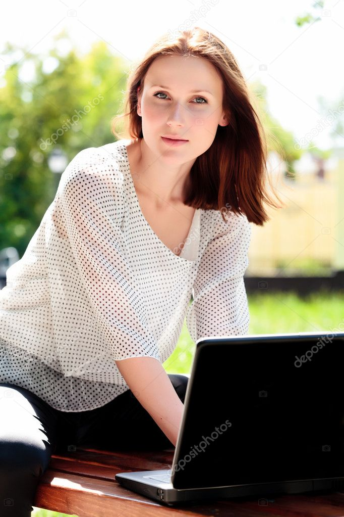 Pretty young woman with a laptop at park — Stock Photo #3389685