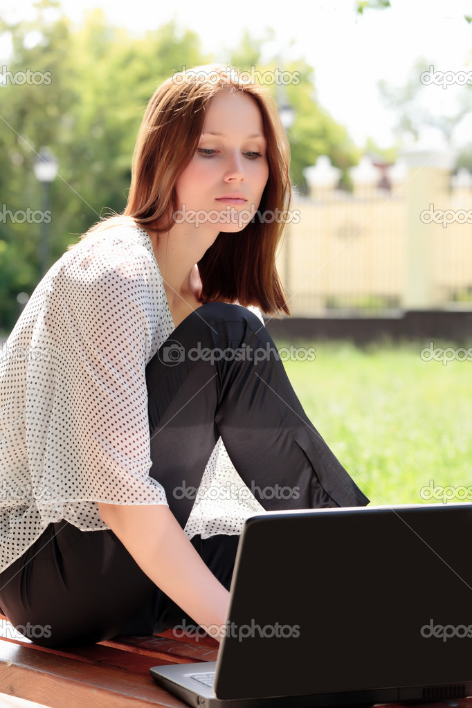 Pretty young woman with a laptop at park  Stock Photo #3389827