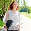 Woman walking with laptop under the hand — Stock Photo