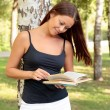 Pretty girl reading a book in a park — Stock Photo