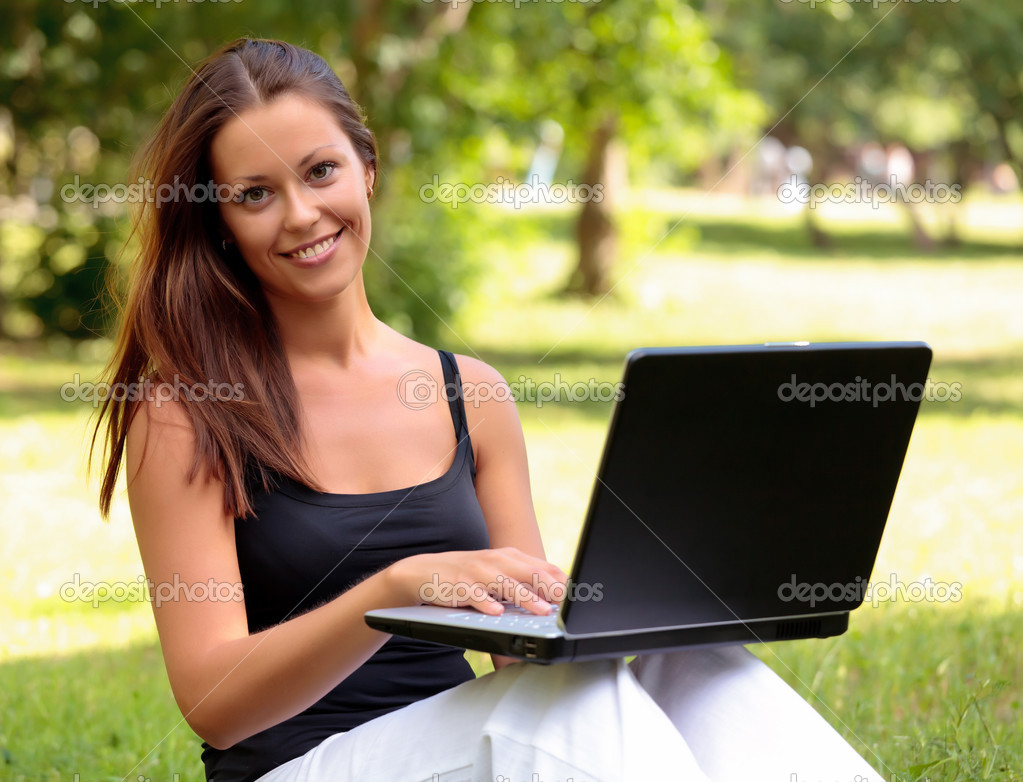 Beautiful young woman sits on a grass in a park with the laptop. — Stock Photo #3416004