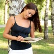Foto Stock: Pretty girl reading a book in a city park