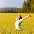 Woman with open arms in the cereal field. — Stock Photo