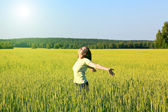 Woman with open arms in the green cereal field. — Stock Photo
