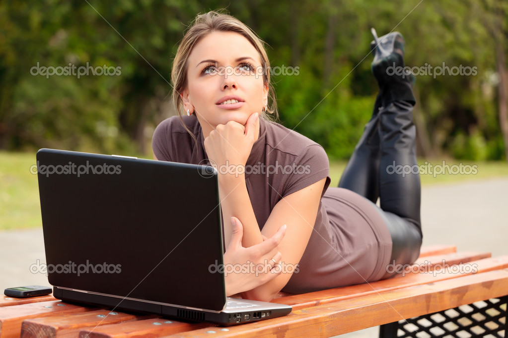 Young pretty woman with laptop lying on the bench in a park — Stock Photo #3465792